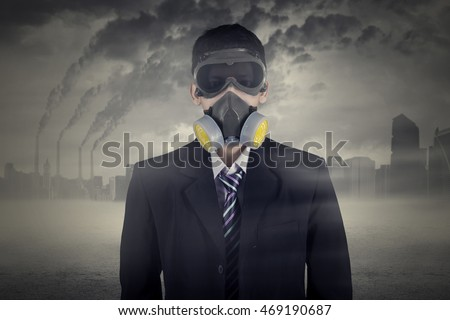 Businessman wearing gas mask with air pollution background in the city