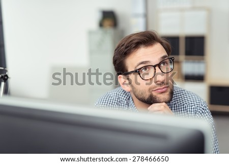 Businessman wearing glasses sitting thinking behind his desktop computer monitor staring thoughtfully up into the air with a serious expression - stock photo