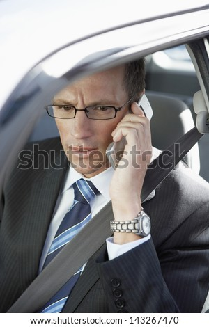 Businessman wearing glasses while using mobile phone in car - stock photo