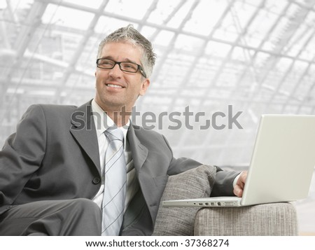 Businessman wearing grey suit and glasses, sitting on couch with laptop computer in office lobby, smiling.