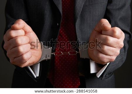 Businessman Wearing Handcuffs Illustrating Corporate Crime