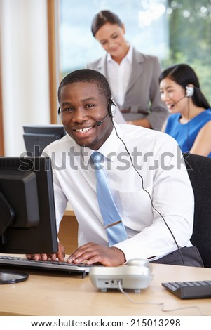 Businessman Wearing Headset Working In Busy Office - stock photo