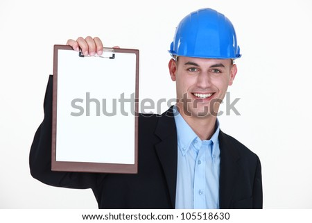 businessman wearing helmet and holding a notepad - stock photo
