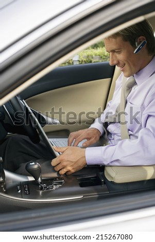 Businessman wearing mobile phone hands-free device, sitting in car, using laptop, side view - stock photo