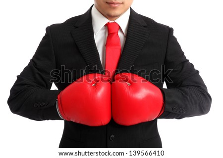 Businessman wearing red boxing gloves and a black suit with a red tie. White background