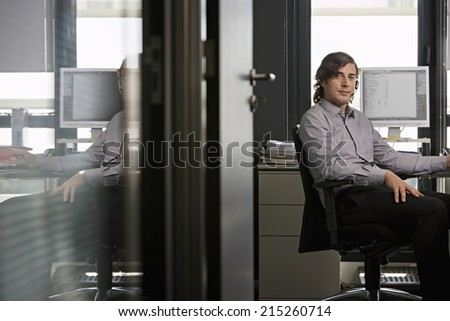 Businessman wearing telephone headset, sitting at desk in office, doorway view, side view, portrait