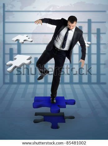 businessman who complete a puzzle on a background with statistics - stock photo