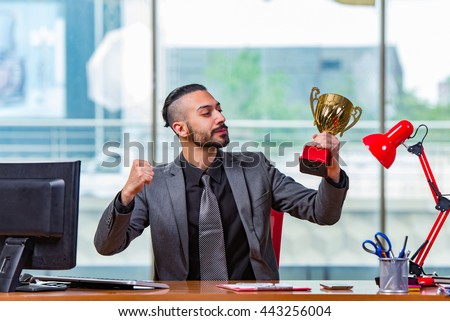 Businessman winning cup trophy in the office - stock photo