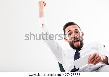 businessman winning something on his smartphone - stock photo