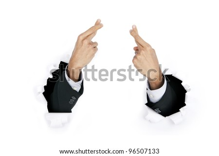 Businessman wishing with the fingers crossed breaking through white paper