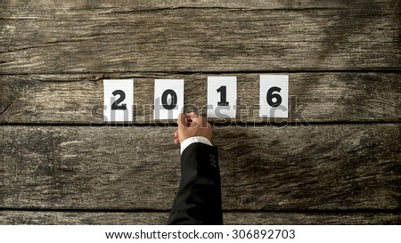 Businessman wishing you Happy New Year for 2016 laying out memo card with the date on a rustic wooden desk or table, close up overhead view of his hand and the date.