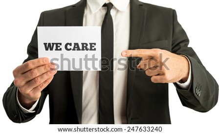 Businessman with a a rectangular white card or sign in his hand saying - We Care - in a conceptual image of business service and quality, closeup of his hands and chest in a suit and tie on white. - stock photo