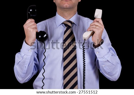 businessman with a black and white telephone receiver in each hand (isolated on black) - stock photo