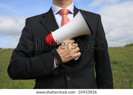 Businessman with a black suit holding a megaphone like gun