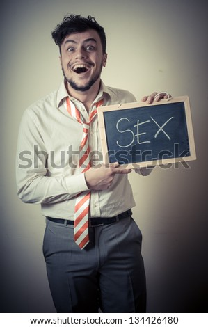 businessman with a blank blackboard write sex on gray background - stock photo