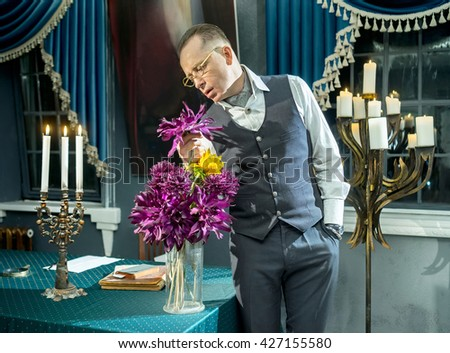 Businessman with a bouquet of flowers in vase on the table