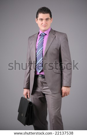 Businessman with a briefcase against grey background - stock photo
