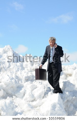 Businessman with a briefcase and phone - on a snow field