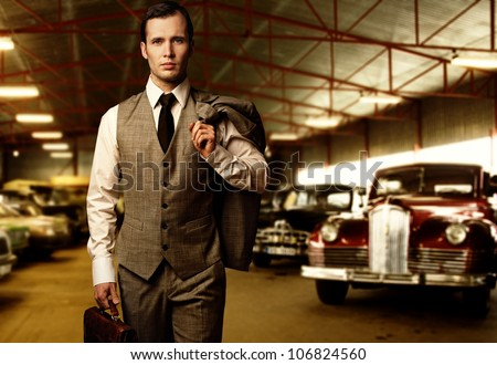Businessman with a briefcase in garage - stock photo