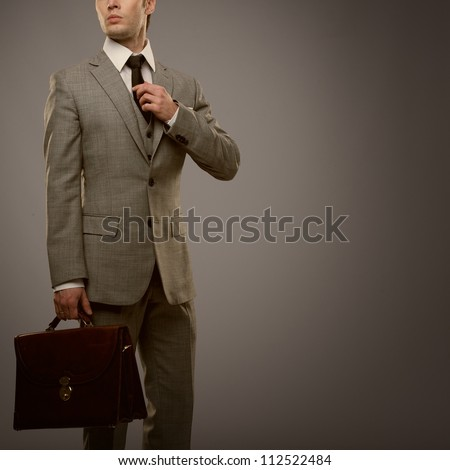 Businessman with a briefcase isolated on grey - stock photo