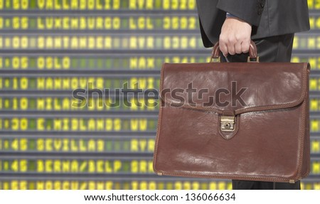 Businessman with a briefcase on a background of departure board at airport - stock photo