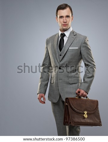Businessman with a briefcase on grey background. - stock photo