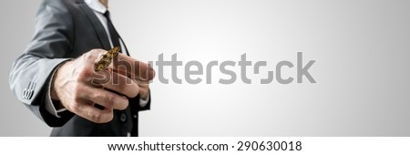 Businessman with a butterfly on his finger holding out his hand towards the camera, low angle view against a grey background with copyspace.