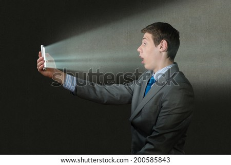 businessman with a cell phone, the light falls on the face of the screen