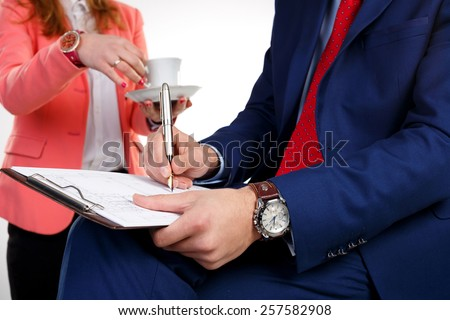 Businessman with a clock on the hand writes the document. In the background, business woman serves coffee. Emphasis on the clock. - stock photo
