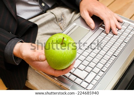 Businessman with a computer and an apple in hand - stock photo