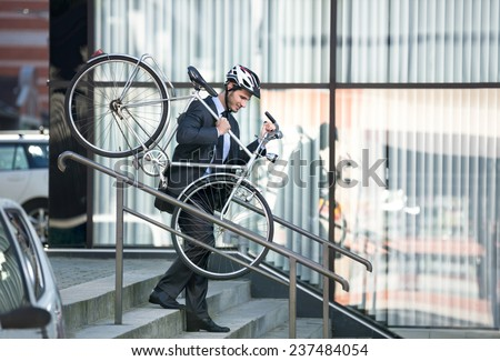 businessman with a cycle helmet on head carrying his bike down steps - stock photo