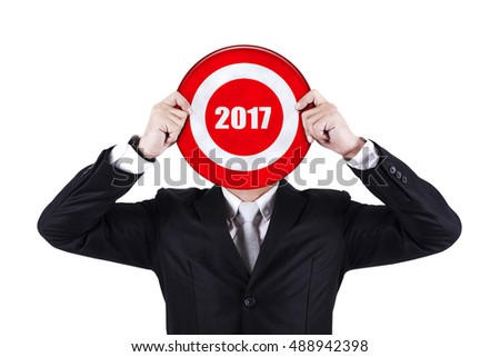 Businessman with a dart in bull's eye, isolated on white background