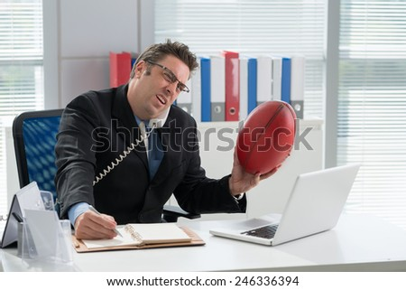 Businessman with a football talking on the phone in the office - stock photo