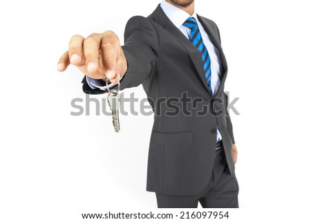 Businessman with a house key in hand isolated on white