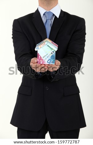 Businessman with a house made out of Euros