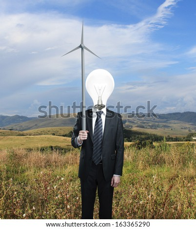businessman with a lamp for a head holding wind turbine - stock photo