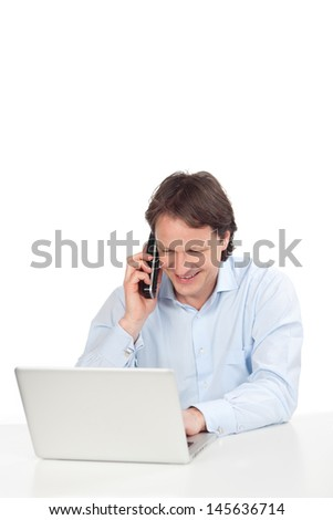 Businessman with a laptop and telephone sitting at his desk having a conversation with a client, over white - stock photo