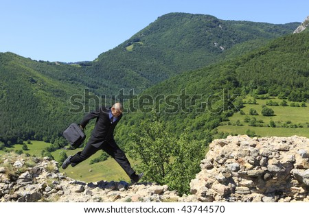 Businessman with a laptop bag running outdoors on a rocky ruined stronghold wall in a mountainous area.