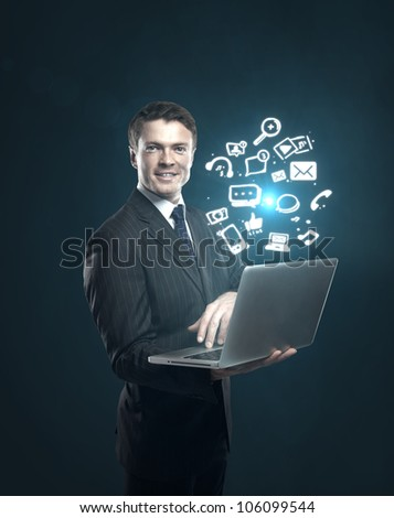 businessman with a laptop in hand and a sign of social networks - stock photo