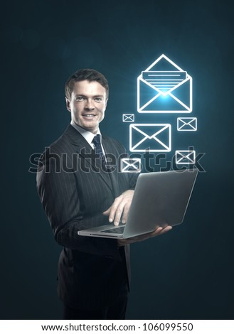 businessman with a laptop in hand and mail symbol - stock photo