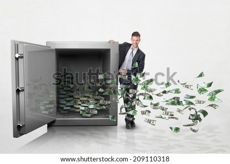 Businessman with a large safe full of money - stock photo