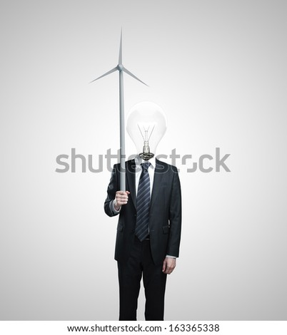 businessman with a light bulb for a head holding wind turbine - stock photo