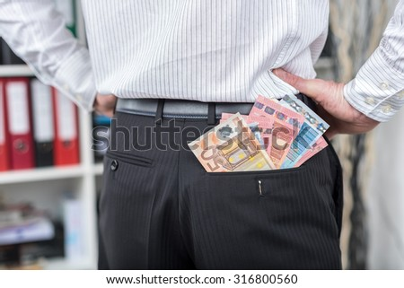 Businessman with a lot of banknotes in his back pocket