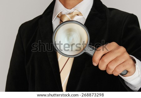 Businessman with a magnifier checking things - stock photo