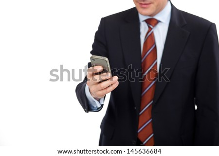 Businessman with a personal organizer or smart phone in his hand browsing the internet or entering data on the touchscreen - stock photo