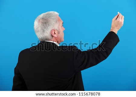 Businessman with a piece of chalk - stock photo