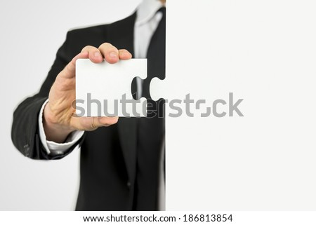 Businessman with a piece of the puzzle standing ready to fit the two matching shapes together in a concept of problem solving and meeting business challenges. - stock photo