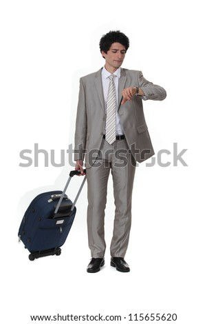 Businessman with a suitcase looking at his watch - stock photo