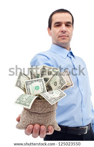 Businessman with a tempting offer - handing you a bag of money, various dollar bills - stock photo