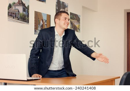 Businessman with a warm friendly smile standing up to shake hands over his desk in welcome, congratulations or to finalize a business deal or partnership